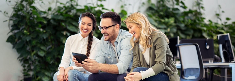 Junge Leute schauen auf ein Tablet.
